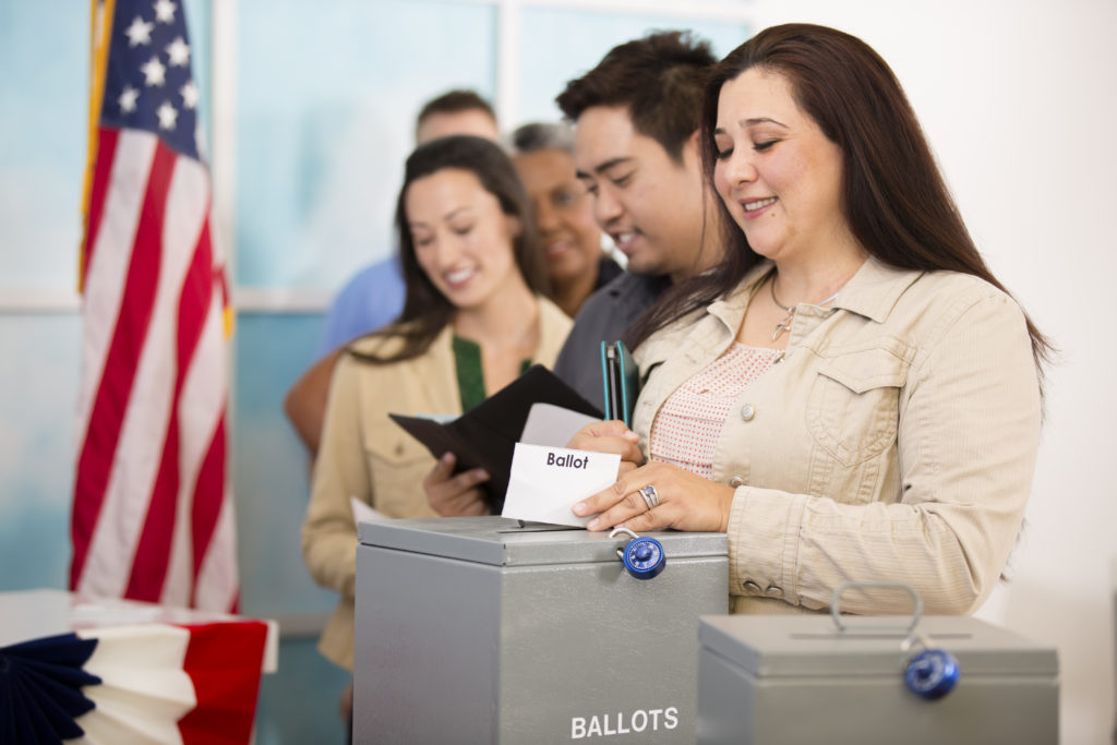 Multi-ethnic group onsite casting in-person vote