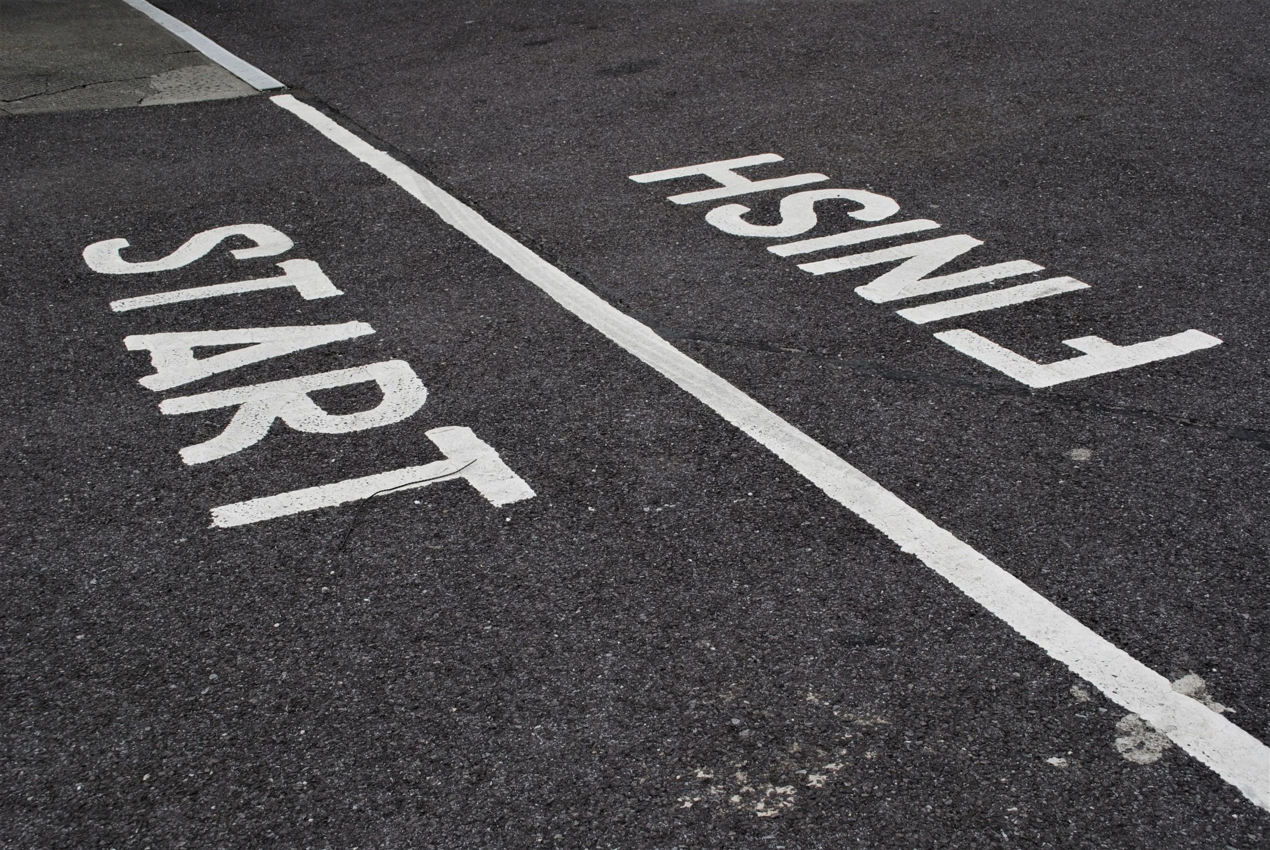 White painted start and finish lines on black tarmac